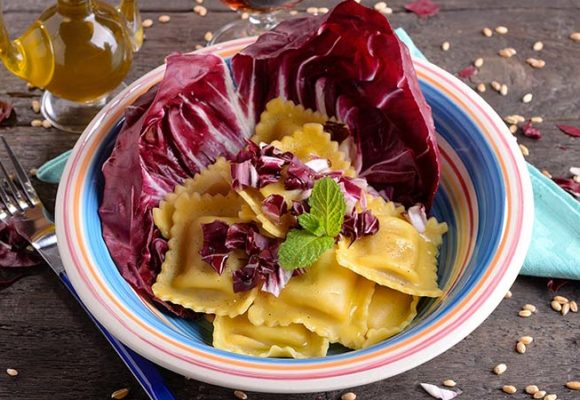 Ravioli with cheese, radicchio and speck sauce
